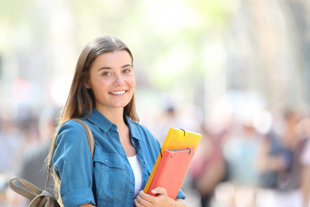 Student posing smiling in the street stock photo