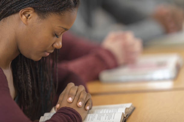Student praying A girl sitting in a high school classroom has her hands clasped together over an open bible on her desk. Her eyes are closed and her head is bowed. catholicism stock pictures, royalty-free photos & images
