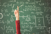 istock Student raised up hand pointing finger in front of green chalk board 944043452