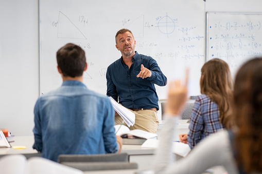 Professor pointing at college student with hand raised in classroom. Student raising a hand with a question for the teacher. Lecturer teaching in class while girl have a question to do during a math lesson.