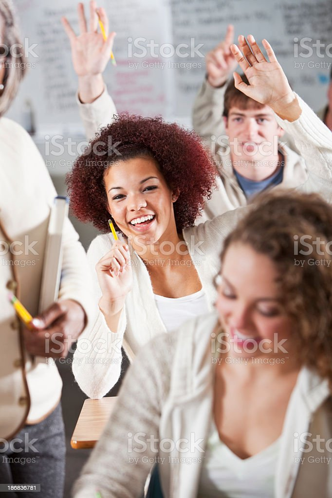 Student raising hands in class royalty-free stock photo