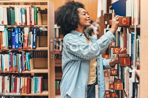 Young African-American ethnicity woman searching books in a library