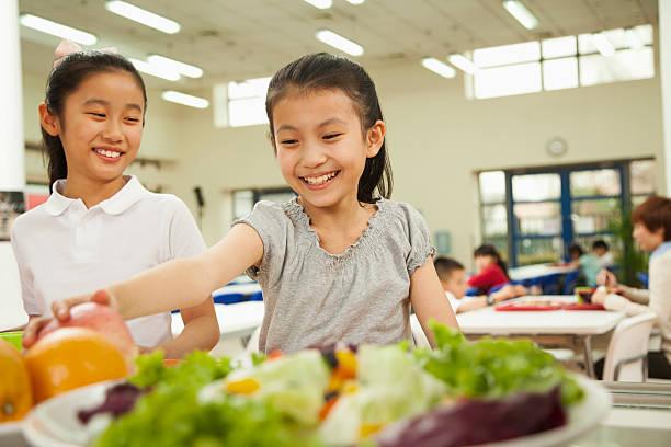 studenten erreichen für eine gesunde speisen in der cafeteria der schule - kantine stock-fotos und bilder
