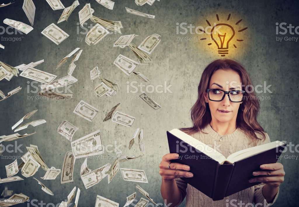 student reading a book has a bright idea how to earn money stock photo