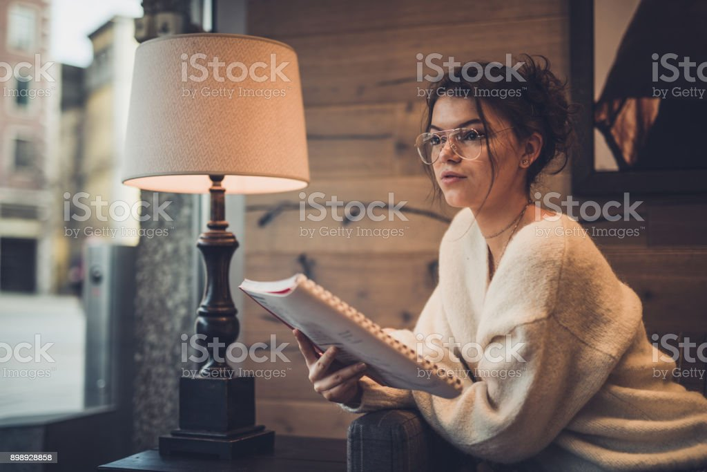 Student reading a book in cafeteria. stock photo