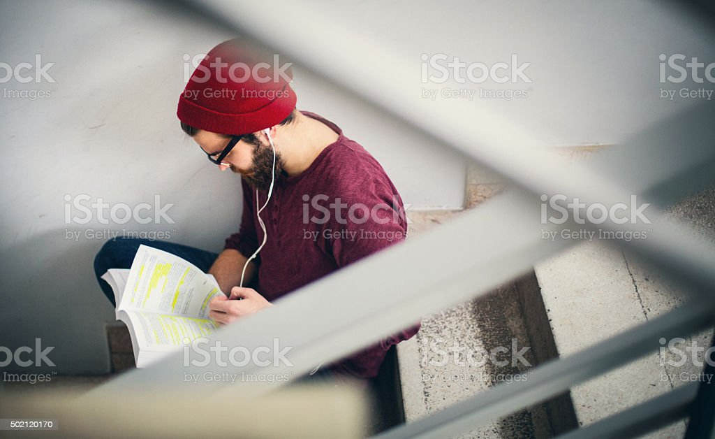 Student reading a book in hallway. stock photo