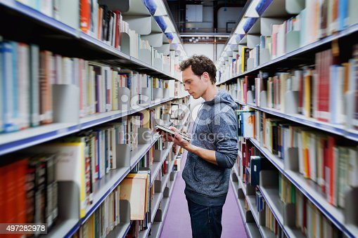 istock student reading book between the shelves in the library 497282978