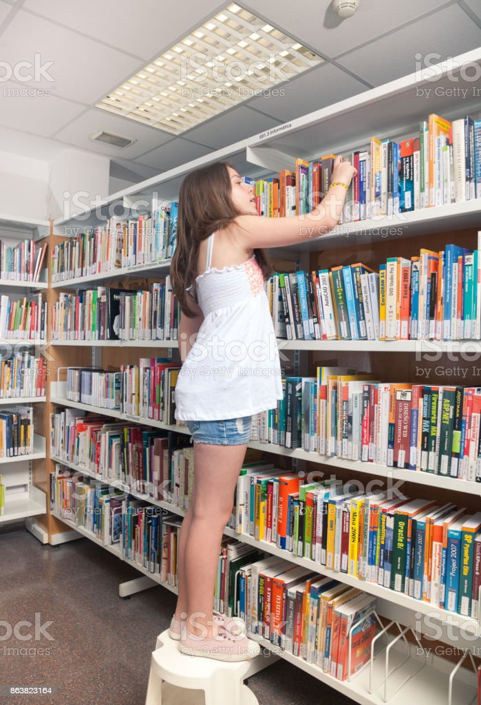 Student reading book between the shelves in the library stock photo