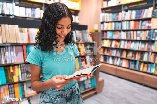 istock Student reading book in library 1180702646