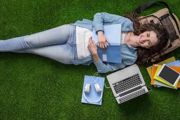 student relaxing on the grass - aree esterne della scuola foto e immagini stock