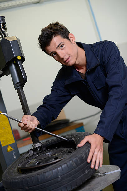 Student repairing tyre in a garage stock photo