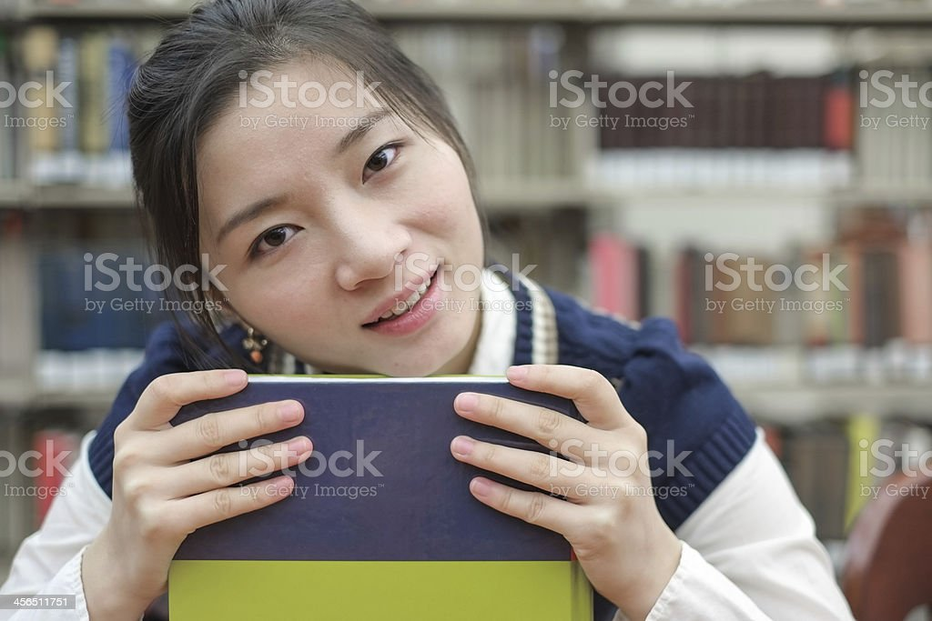 Student resting her chin on textbook royalty-free stock photo