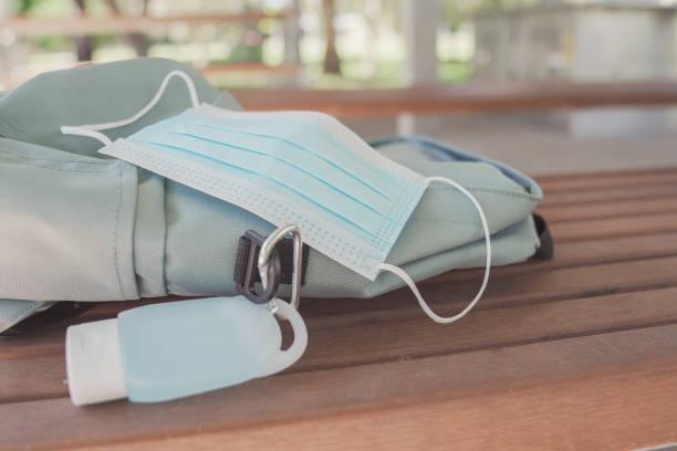 Schüler-Schultasche mit Handdesinfektionsclip auf, Schuleröffnung, Rückkehr in die Schule nach covid-19 Coronavirus Pandemie vorbei, neues normales Konzept – Foto
