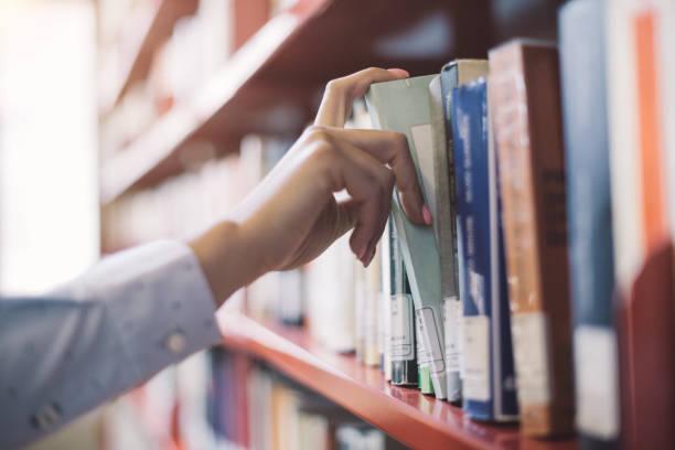 estudiantes que buscan libros - biblioteca fotografías e imágenes de stock