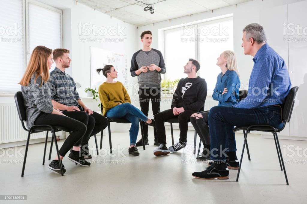 Student seeking advice in mental health therapy Young male student seeking for advice in mental health therapy session. Students and mental health professional are sitting in lecture hall. They are in university. 18-19 Years Stock Photo