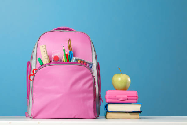 student set. pink backpack with stationery, a stack of books, a lunchbox, an apple on the table on a blue background. back to school. - cartella scolastica foto e immagini stock
