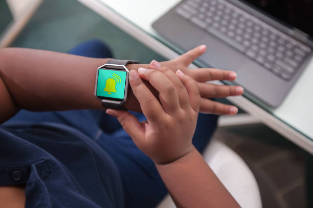 A student sitting at a desk looks at wristwatch alarm to pace and time manage. stock photo