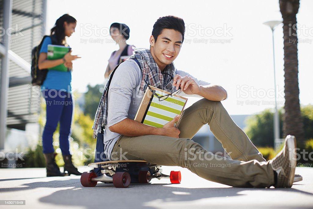 Estudante sentada no skate ao ar livre - foto de acervo