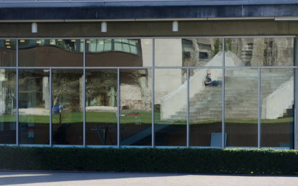 Student sitting on stairs reflected in glass wall of a building in campus n Bellingham stock photo