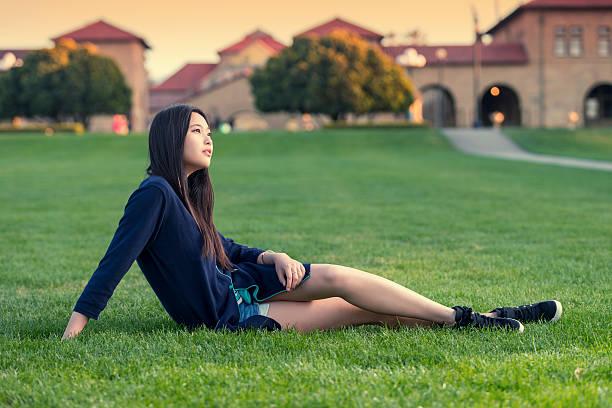 Estudante sentada no gramado de campus - foto de acervo