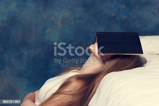 istock Student sleeps covering face with book near a bed. The student has fallen asleep. Reweariness, reading house 865261464