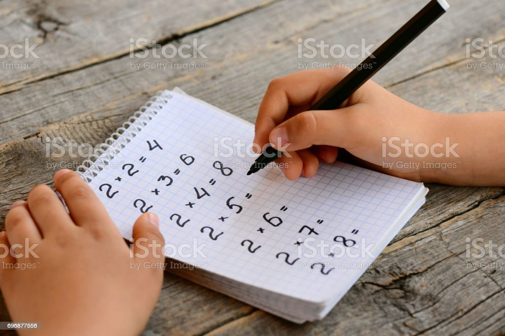 Student solves multiplication examples. Child holds a black marker in his hand and writes answers. Notebook with multiplication table examples. Teaching a multiplication table concept stock photo