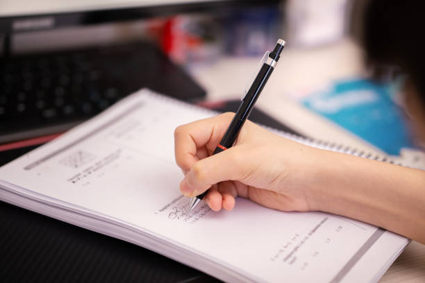 student solving questions and doing homework at home stock photo