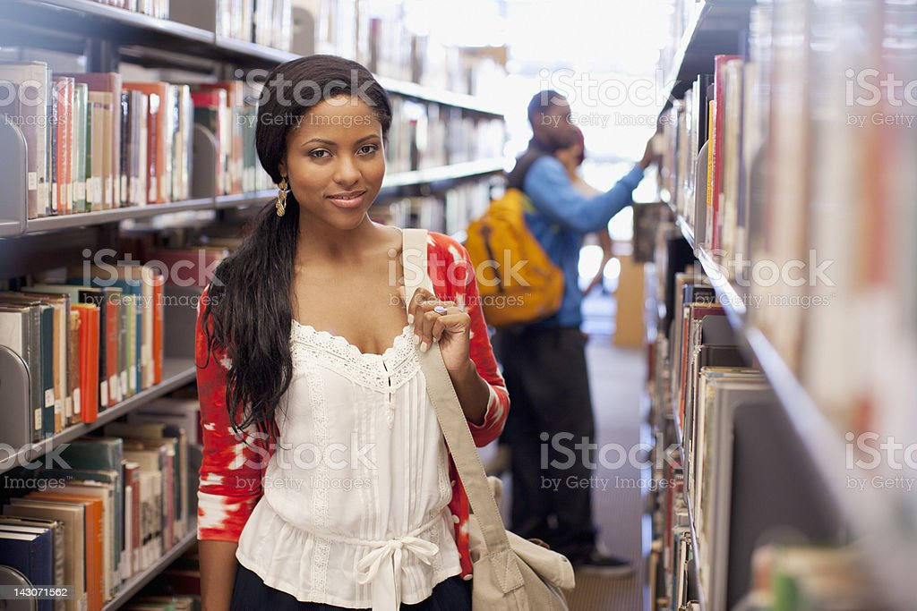 Student standing in library royalty-free stock photo