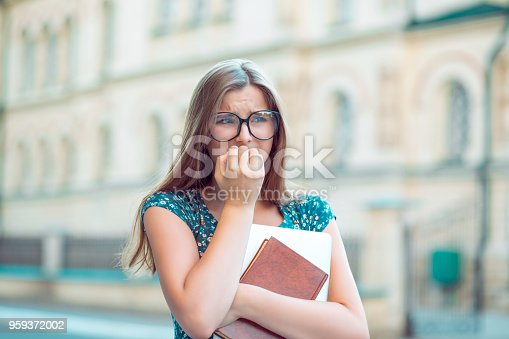 istock Student stressed young woman biting fingernails looking away anxiously 959372002