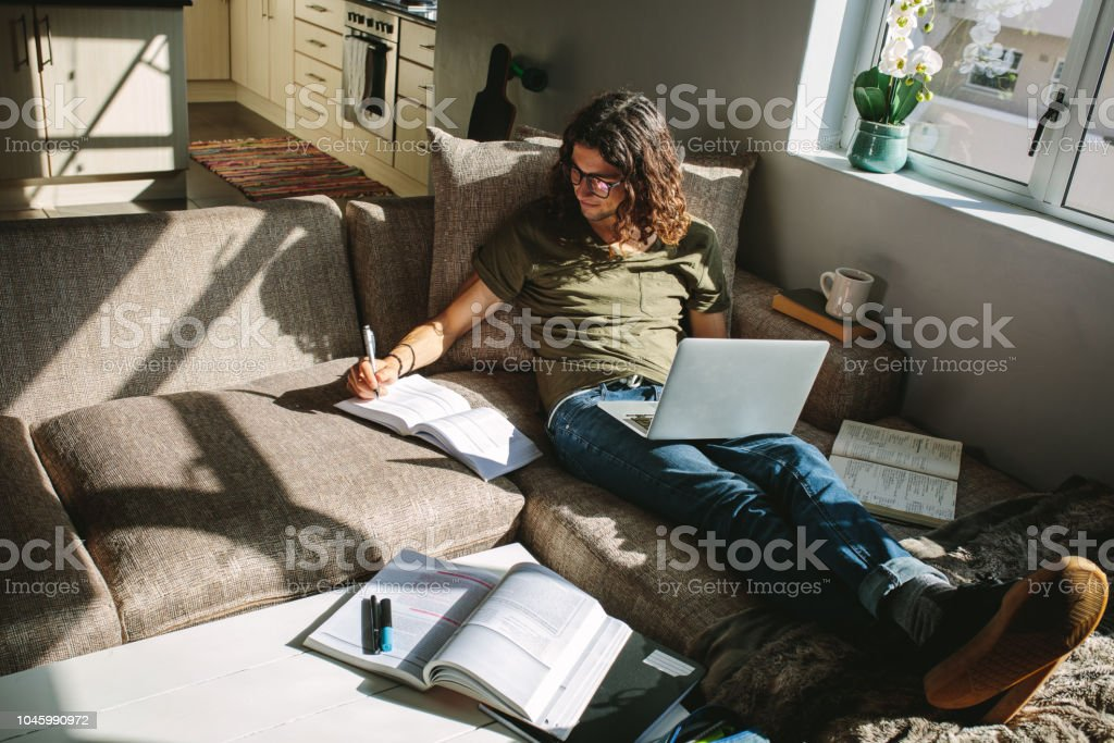 Student studying at home sitting beside a window stock photo