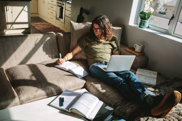 Studierender zu Hause neben einem Fenster – Foto