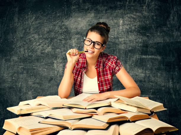 studentessa che studia libri, giovane donna universitaria leggi molti libri sulla lavagna - esame maturità foto e immagini stock