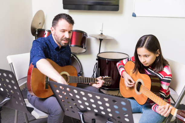 Student Studying Music As A Hobby Music teacher giving instruction in instrumental music to preteen girl at guitar class middle school teacher stock pictures, royalty-free photos & images