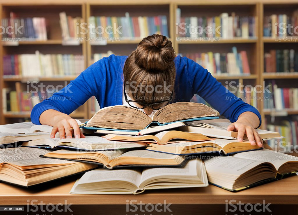 Stock photo showing person with head on a pile of books.