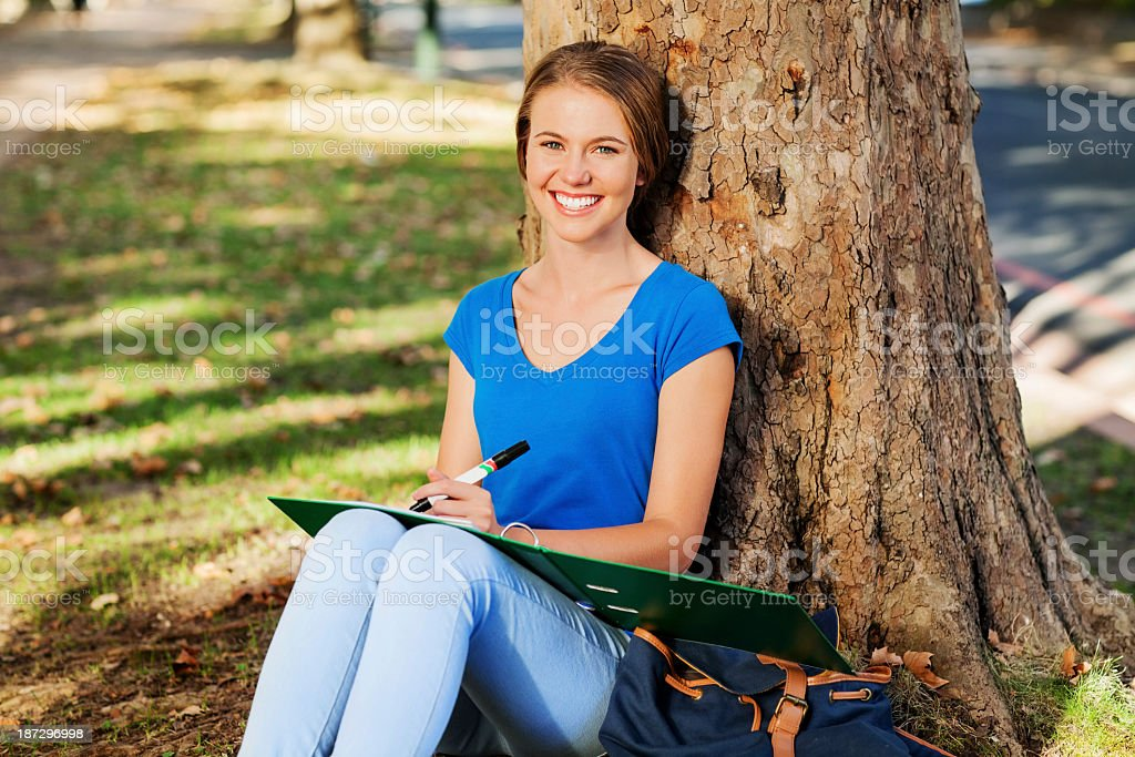 Student Studying While Sitting Against Tree On College Campus royalty-free stock photo