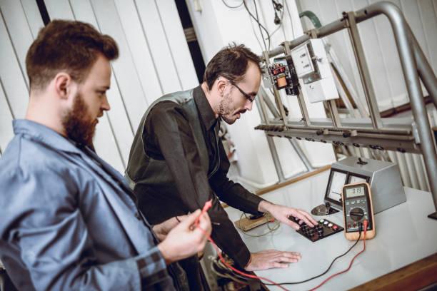 estudiante tomar el examen práctico en la clase de ingeniería eléctrica - suministros escolares fotografías e imágenes de stock