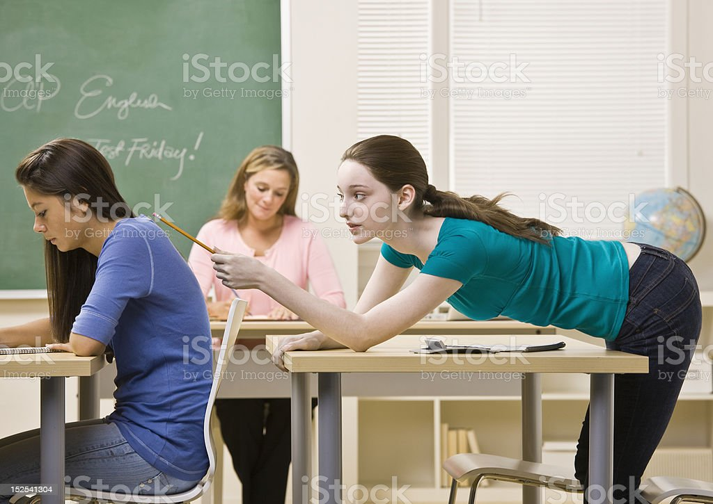 Student Tapping Classmate in Classroom royalty-free stock photo
