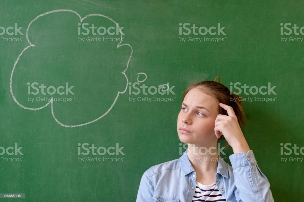 Student thinking blackboard concept. Pensive girl looking at thought bubble on chalkboard background. Caucasian student. stock photo