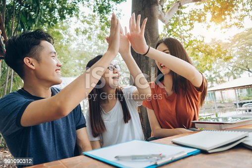 istock Student university success high-five project concept, students asian working complete and finish job happy feeling with friends smiling at campus high school college 991090312
