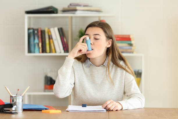 Student using an asthma inhaler at home stock photo