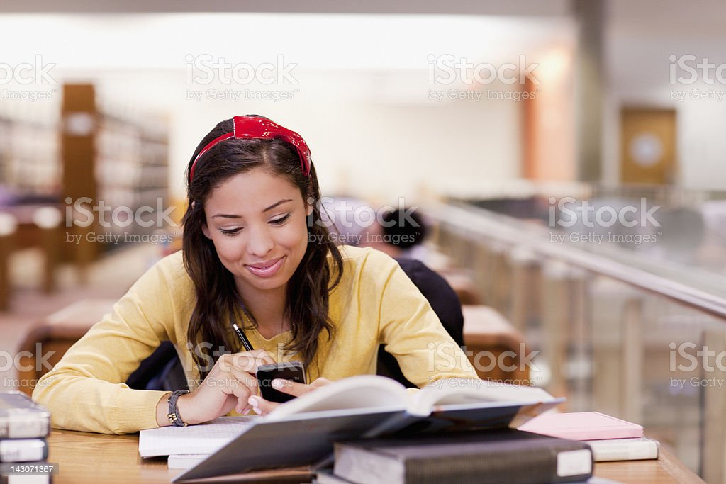 Student using cell phone and studying in library royalty-free stock photo