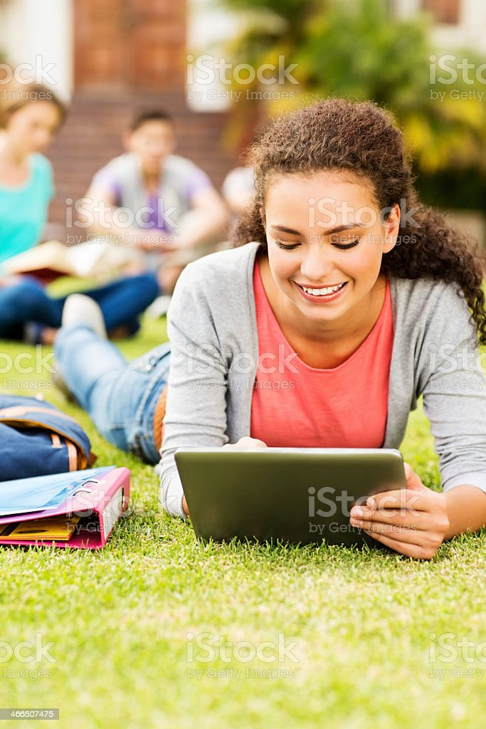 Student Using Digital Tablet While Lying On Campus stock photo