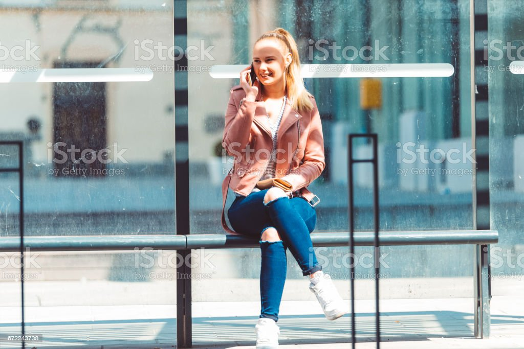 Student using mobile at the bus shelter stock photo