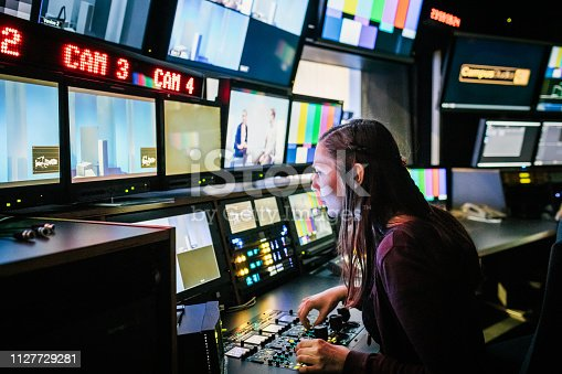 A university student looking at various screens while using tv studio equipment.