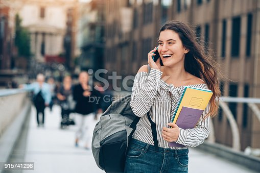istock Student walking and talking on the phone 915741296