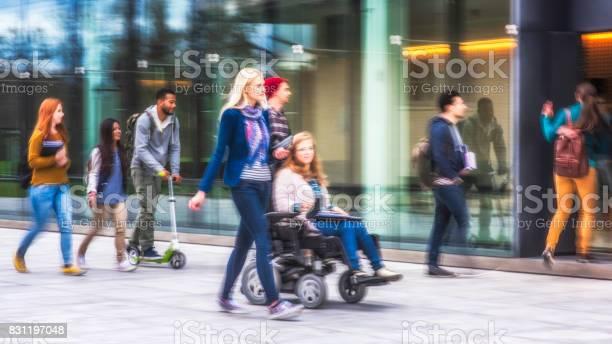 Student walking beside a friend with disability picture id831197048?b=1&k=6&m=831197048&s=612x612&h=3sxzcj5hiowxnqj ztqlujbwu8fezro39 qzl95j5n0=