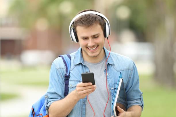 schüler zu fuß lernen mit audio-lektionen - one song training stock-fotos und bilder