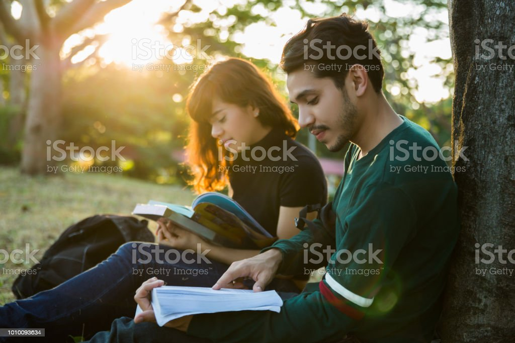 Student was reading in the outdoors and good weather. And they're happy.lens flare stock photo