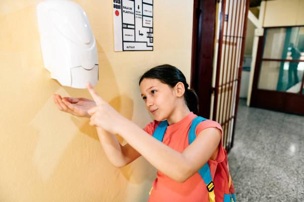 Schüler waschen Hände mit Handdesinfektionsmittel in der Schule – Foto