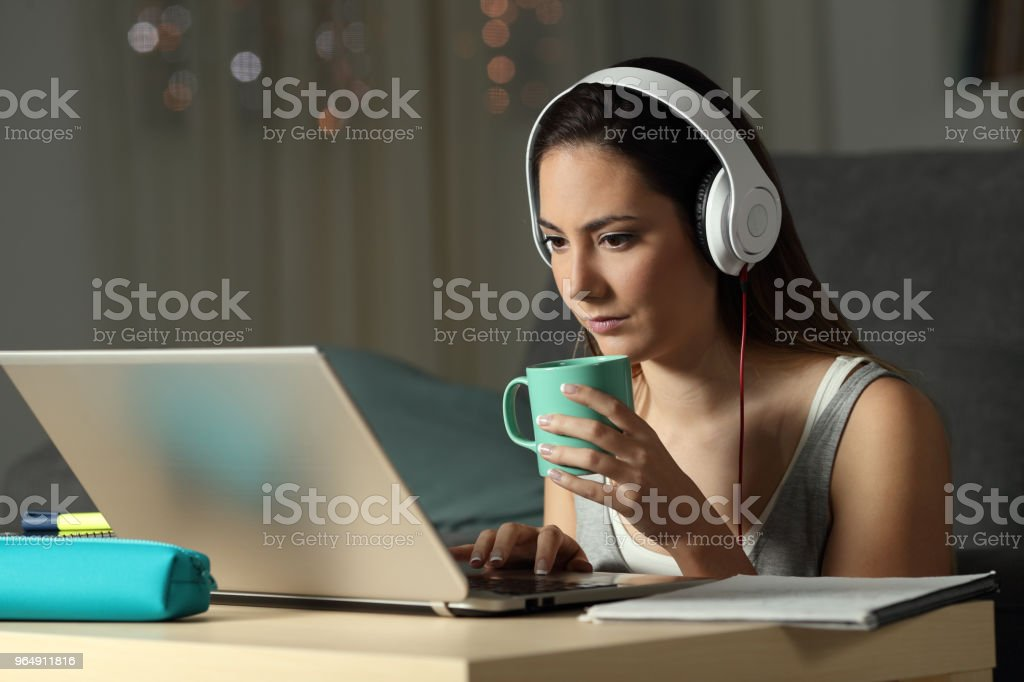 Student watching video tutorials in the night royalty-free stock photo